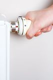 Men adjusting thermostat on home radiator. Save environment and reduce home temperature Stock Photos
