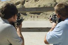 Men Aiming Rifles At Firing Range. Rear view of two men aiming rifles at firing range during combat training Royalty Free Stock Image