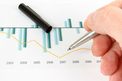 Men analyzing business graph. Men analyzing red and grey business graph, business concept Royalty Free Stock Images