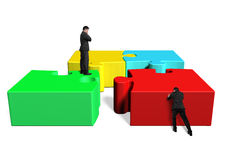 Men assembling four puzzles. Assembling four puzzles  in white background Royalty Free Stock Images