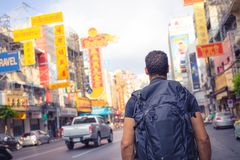 Men backpacker looking at Yaowarat road in Bangkok during day, Thailand , Southeast asia . stock photo