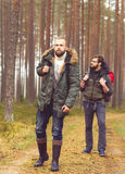 Men with backpacks and beards hiking in the forest. Camp, adventure, traveling concept. Man with a backpack and beard hiking in forest. Autumn color and hipster stock image