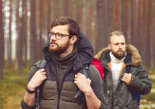 Men with backpacks and beards hiking in the forest. Camp, adventure, traveling and friendship concept. Man with a backpack and beard and his friend hiking in stock photo