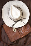Men bag with straw hat on wooden background. Summer accessories, bag and straw hat Stock Image