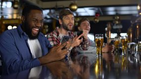 Men in bar celebrating successful bet on sports, using online bookmaker on phone