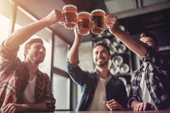 Men in bar. Cheers, my friends! Three handsome men are drinking beer, celebrating meeting and smiling royalty free stock photos