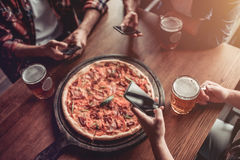 Men in bar. Cropped image of three male friends in bar are drinking beer and eating pizza with smartphone in hands stock images