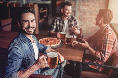Men in bar. Happy handsome men in bar is drinking beer, smiling and looking at camera royalty free stock photography
