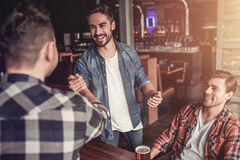 Men in bar. Happy to finally meet old male friends in bar. Shaking hands and smiling Stock Photography