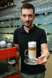 Men barista hold glass of latte. Serving a client. Stock Photography
