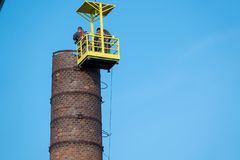 Men in a basket hanging from a gigantic crane, painstakingly removing a factory chimney. 2 men in a basket hanging from a gigantic crane, painstakingly removing royalty free stock photos