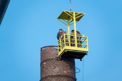 Men in a basket hanging from a gigantic crane, painstakingly removing a factory chimney. 2 men in a basket hanging from a gigantic crane, painstakingly removing royalty free stock photo