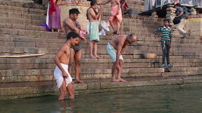 Men bathing on the ghats of Ganges river in Varanasi. VARANASI, INDIA - 22 FEBRUARY 2015: Men bathing on the ghats of Ganges river in Varanasi stock video footage