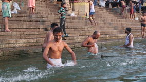 Men bathing on the ghats of Ganges river in Varanasi. VARANASI, INDIA - 22 FEBRUARY 2015: Men bathing on the ghats of Ganges river in Varanasi stock footage