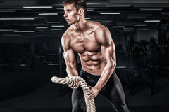 Men with battle rope battle ropes exercise in the fitness gym. CrossFit. royalty free stock photo
