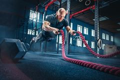 Men with battle rope battle ropes exercise in the fitness gym. royalty free stock photo