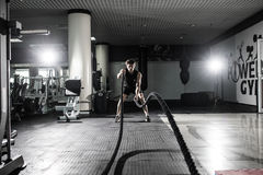 Strong Men with battle rope battle ropes exercise in the fitness gym. CrossFit. Men with battle rope battle ropes exercise in the fitness gym. CrossFit Royalty Free Stock Images