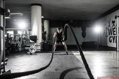 Strong Men with battle rope battle ropes exercise in the fitness gym. CrossFit. stock photos