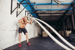 Men with battle rope battle ropes exercise in the fitness gym. Cross Fit Stock Photo