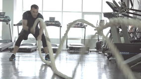 Men with battle rope in functional training fitness gym stock video