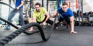 Men with battle rope in functional training fitness gym. Men with battle rope in functional training fitness in gym Royalty Free Stock Photos