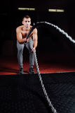 Men with battle rope in functional training fitness gym stock photo