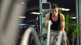 Men with battle rope in functional training fitness gym. young cute model. Slender, gray shorts, black shirt. indoor close-up stock footage