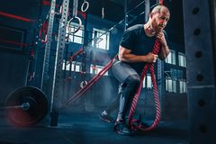 Men with battle rope battle ropes exercise in the fitness gym. CrossFit. stock photography