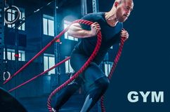 Men with battle rope battle ropes exercise in the fitness gym. royalty free stock image