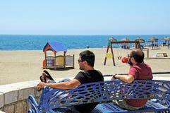 Men on beach by sea, Malaga, Spain. Stock Photos