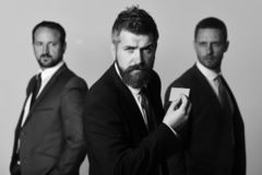 Men with beard and determined faces advertise company and partnership. Career and self presentation concept. Executives hold business card on light grey stock photos
