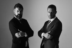 Men with beard and determined faces express confidence and partnership. Leaders hold hands crossed on light grey background. Argument and business concept stock photo