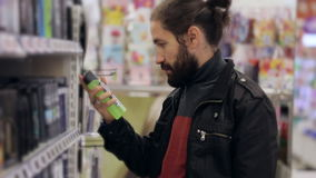 Men with beard and long hair selecting antiperspirant in supermarket.
