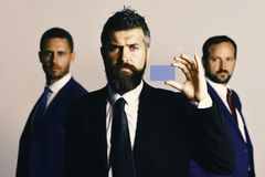 Men with beard and serious faces advertise company and partnership. Leaders hold business card on light grey background. Leadership and presentation concept royalty free stock images