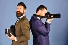 Men with beards hold photo cameras on blue background. Business or promotion concept. Reporters in classic suits work on event. Businessmen with confident royalty free stock images