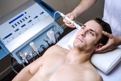 Men in a beauty clinic. Men in a clinic by becoming a beauty treatment Royalty Free Stock Images