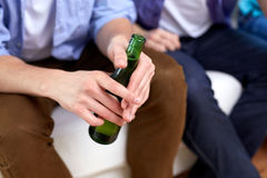 Men with beer bottles sitting on sofa at home Royalty Free Stock Image