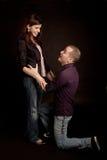 Men begging girlfriend. Studio shot royalty free stock images