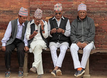 Men on a bench. Four men sitting on a bench in india.Two men watching a mobile.They wear traditional clothes Stock Photos
