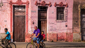 Men on bicycles in Cuban street. Camaguey, Cuba on January 3, 2016: Cuban men riding bicycles through a street in the historic Caribbean city center of Camaguey Royalty Free Stock Photos
