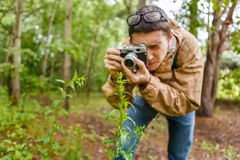 Men biologist in glasses photograph plants. In summer forest Royalty Free Stock Image
