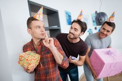 Men in birthday hats are preparing a surprise birthday party. They are preparing to meet the birthday girl. They are holding a presents in their hands Royalty Free Stock Photo