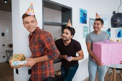 Men in birthday hats are preparing a surprise birthday party. They are preparing to meet the birthday girl. They are holding a presents in their hands Stock Photos