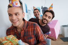 Men in birthday hats are preparing a surprise birthday party. They are preparing to meet the birthday girl. They are holding a presents in their hands Stock Photo