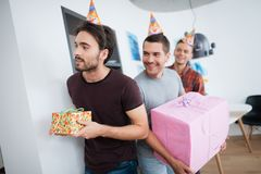 Men in birthday hats are preparing a surprise birthday party. They are preparing to meet the birthday girl. They are holding a presents in their hands Royalty Free Stock Photos