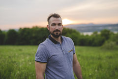 Men with a black beard on a meadow. A man with a black beard on a meadow Stock Image