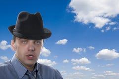 Men in black hat on blue sky Stock Image
