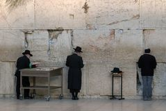 Men in black traditional Jewish hats and frock coats pray near the Western Wall, Jerusalem, Israel. Stock Images