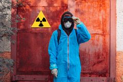 Man environment mask face radiation facemask icon protective overall blue orange rast factory disused catastrophe. Men in blue protective overall near icon of royalty free stock images