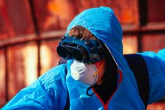 Man environmental mask fire pack disguise facemask bitmask protective overall blue orange rast plant factory disused catastrophe. Men in blue protective overall royalty free stock image